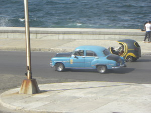 Vintage taxi and coco-taxi strolling down Havana's waterfront.